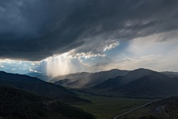 Scenic top view on the valley between the mountains, hills covered with vegetation, forest, storm clouds and sunlight