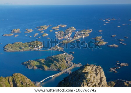 Scenic town of Henningsvaer on Lofoten islands in Norway with large fishing harbour and bridges connecting rocky islands