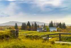 Scenic valley and a village in Thingvellir National Park - famous area in Iceland. with some of tourist during autumn