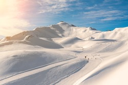 Scenic valley of hilghland alpine mountain winter resort on bright sunny day. Wintersport scene with people enjoy skiing and snowboarding on groomed pisets. panoramic wide view of downhill slopes