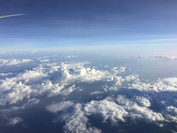 Scenic view above the clouds during a commercial flight. Atmosphere beautiful blue sky . Flying above the clouds, blue sky. High angle air. Background Cloud. A view from airplane.