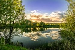 Scenic view at beautiful spring sunset on a shiny lake with green branches, birch trees, bushes, grass, golden sun rays, calm water ,deep blue cloudy sky and forest on a background, spring landscape