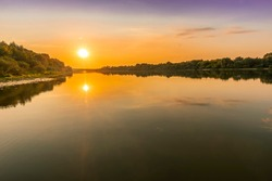 Scenic view at beautiful summer river sunset with reflection on water with trees , golden sun rays, calm water ,deep blue cloudy sky and glow on a background, spring evening landscape