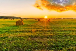 Scenic view at beautiful sunset in a green shiny field in willage farm with hay stacks, cloudy sky, golden sun rays, anazing summer valley evening landscape