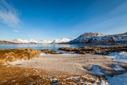Scenic view at the small beach with sand and rocks covered with ice. Snowy mountains and bright blue sky in the background. Spring landscape with melting snow and ice. Arctic Circle, Sommaroy, Norway