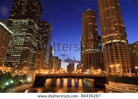 Scenic view from a Chicago River bridge after sunset.  Historic skyscrapers along the River with a deep blue sky in downtown Chicago.