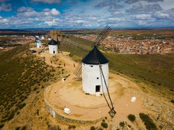 Scenic view from drone of ancient windmills and castle ruins atop Cerro Calderico ridge, Consuegra, Spain