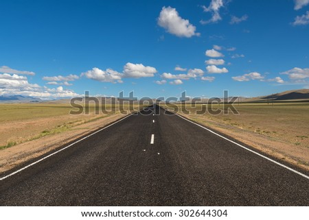 Scenic view from the asphalt road in the steppe on a background of mountains and blue sky with clouds