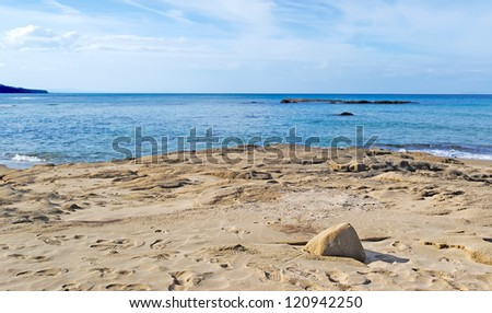 scenic view of a beach with sand under a cloudy sky