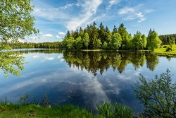 Scenic view of a Kladska lake in the Czech Republic, close to Marianske Lazne surrounded with forest. Sunny summer landscape with blue sky and white clouds and reflection in water.