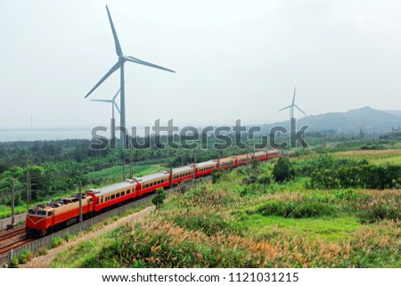 Scenic view of a train traveling by green farm fields and giant wind turbines standing by the beach in a seaside park along the windy coast under hazy summer sky, in Houlung, Miaoli, Taiwan, Asia