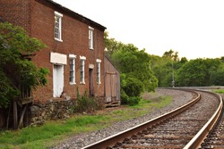 scenic view of an old abandoned railroad building next to a railroad track. Daytime at sunrise or sunset with overgrown vegetation and trees visible. Historic brick rail station, warehouse, or depot.