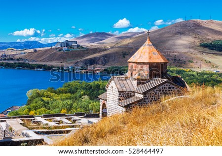 Scenic view of an old Sevanavank church in Sevan, Armenia on sunny day blue sky and fluffy clouds #528464497