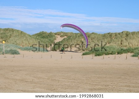 Scenic view of beach with sand dunes and a paraglider in the distance