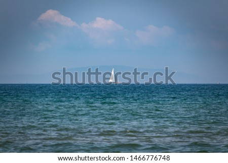 Scenic view of beautiful blue sea against sky.  Sailboat on background. Follonica, Grosseto, Tuscany Italy #1466776748