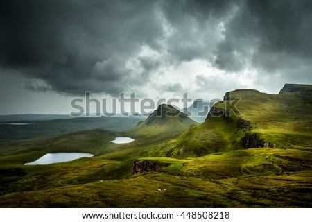 Scenic view of beautiful landscape the Quiraing, Isle of Skye, Scotland from above with view into the valley and hills in the background and dramatic clouds in the sky
