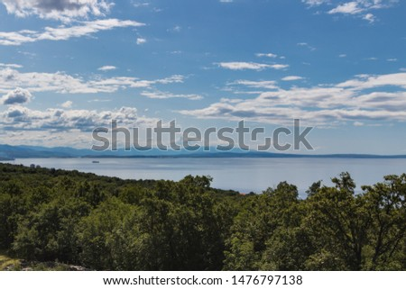 Scenic view of beautiful nature: green leaves, silver sea against blue cloudy sky and Cres island on background. Croatia #1476797138