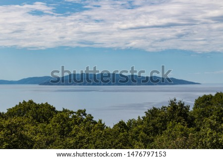 Scenic view of beautiful nature: green leaves, silver sea against blue cloudy sky and Cres island on background. Croatia #1476797153