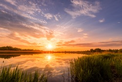 Scenic view of beautiful sunrise or dawn above the pond or lake at spring or early summer morning with cloudy sky background, fog over water and reed grass with dew at foreground. Water reflection.