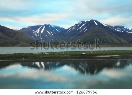 Scenic view of black rocks with melting snow and colorful dramatic sky reflected in calm water of Advent Bay near Longyearbyen, Norway, Spitsbergen archipelago (Svalbard island), Norway, Greenland sea