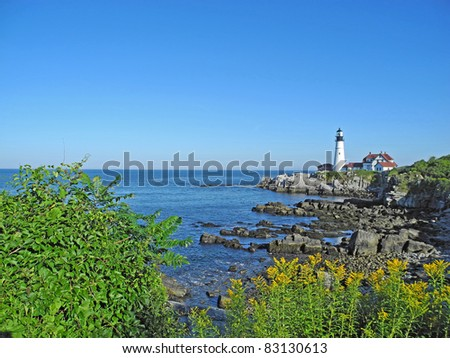 Scenic view of boulders, cliffs, water and sky at Portland Head Light at Fort Williams, in beautiful Portland, Maine. - stock photo