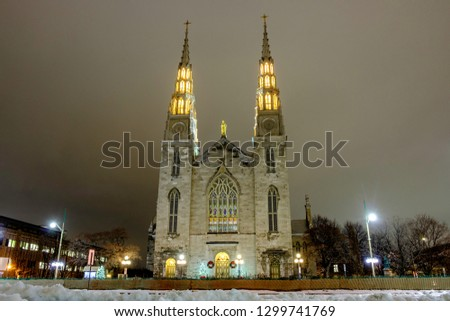 Scenic view of cathedral of Ottawa (Notre-Dame de Ottawa) in capital of Canada. Depressive beautiful winter look of old historic famous catholic temple covered by snow in nighttime illumiantion #1299741769