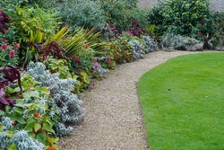 Scenic View of Colourful Flower Beds, Lush Green Grass Lawn and Winding Pathway in a Beautiful English Style Garden