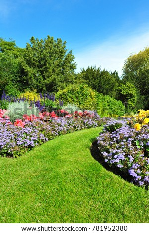 Scenic View of Colourful Flowerbeds, a Lush Green Lawn and a Winding Grass Pathway in a Beautiful English Style Formal Garden