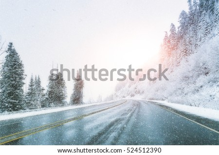 Stock Photo scenic view of empty road with snow covered landscape while snowing in winter season.