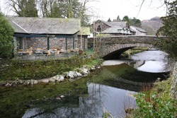 Scenic view of Grasmere village with houses, bridge and ducks floating on the river during early Spring in Ambleside town, Windermere, Lake District National Park, Cumbria, England UK