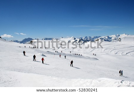 Scenic view of group of skiers on Alpine ski slope with blue sky background.