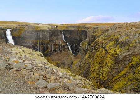Scenic view of Haifoss and Granni - waterfalls in Fossa river in the Thjorsardalur valley, Iceland. The viewpoint on the sheer cliffs at the edge of canyon with a view of Haifoss and Granni waterfalls