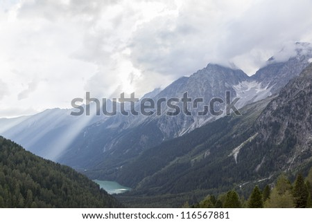 Scenic view of Hochgall mountain range with high peaks, valley and lake in Italian Alps, sunbeams penetrating the clouds.