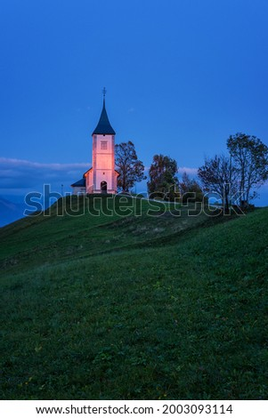 Scenic view of illuminated Jamnik church St Primus and Felician on the hill at dusk, Alps mountains, Slovenia. Beautiful landscape with blue sky, outdoor travel background, famous tourist attraction Zdjęcia stock ©