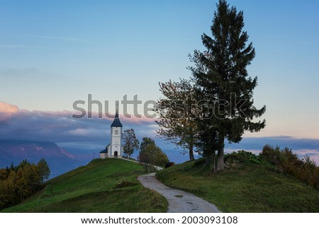 Scenic view of Jamnik church St Primus and Felician at sunset, Alps mountains, Slovenia. Beautiful landscape with footpath and sky with clouds, outdoor travel background, famous tourist attraction Zdjęcia stock ©