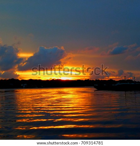Scenic view of lake against dramatic sky at sunset #709314781