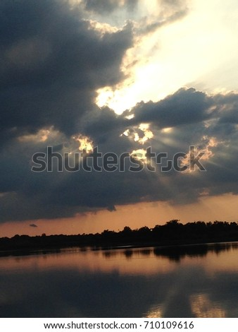 Scenic view of lake against dramatic sky at sunset #710109616