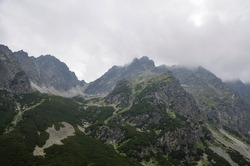 Scenic view of landscape and rocky foggy mountains against cloudy sky in High Tatras, Slovakia