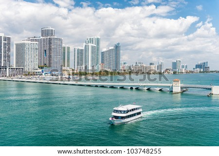 Scenic view of Miami city skyline with boat sailing in foreground sea, Florida, U.S.A.