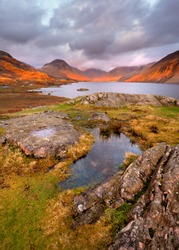 Scenic view of mountains and lake at sunset with golden light and moody clouds. Wastwater, Lake District, UK.