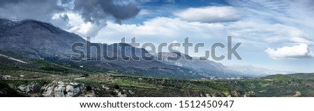 Scenic view of mountains and landscape against sky with clouds