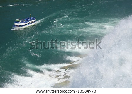Scenic view of Niagara falls with boat full of tourists
