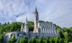 Scenic view of old catholic cathedral in small ancient french historic town Lourdes - world pilgrimage center