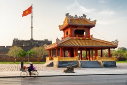 Scenic view of Phu Van Lau Pavilion (Pavilion of Edicts) in front of the Flag Tower of the Citadel in Hue, Vietnam. The flag of Vietnam (red flag with a gold star) fluttering over the Citadel.