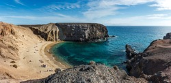 Scenic view of rock cliffs at Playa del Papagayo (Parrot Beach). Lanzarote, Canary Islands, Spain.