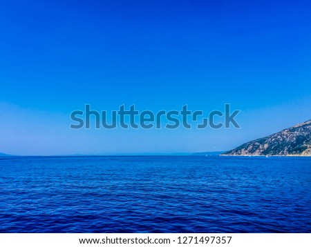 Scenic View of Sea And Land Against Clear Blue Sky #1271497357