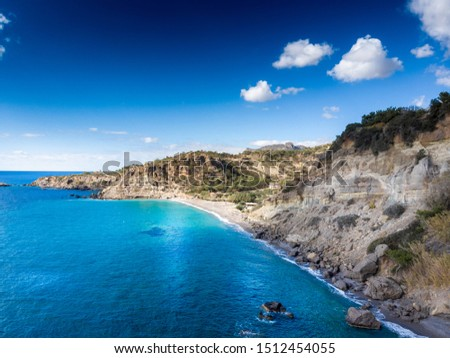 Scenic view of sea and rocky mountain against cloudy sky, Crete, Greece