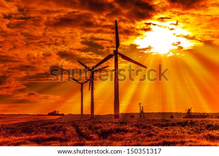 Scenic view of silhouetted wind turbines with orange sunset background.