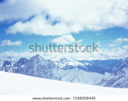 Scenic view of snowy mountains under blue sky