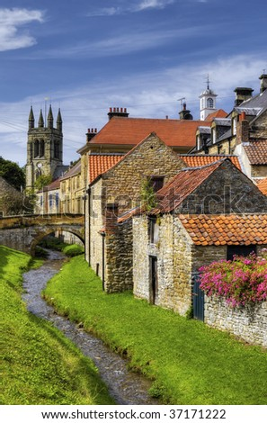 Scenic view of stream running past Helmsley town with church in background, Ryedale, North Yorkshire, England.